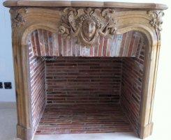 Cheminée en bois style Louis 15 avec foyer ouvert en briquettes anciennes