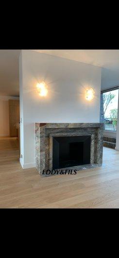 réalisation d'une cheminée en marbre de saracolin opera  comtemporaine sur mesure foyer acier noir