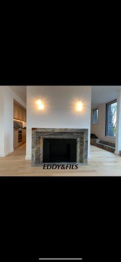réalisation d'une cheminée en marbre de saracolin opera  comtemporaine sur mesure foyer fonte  noir